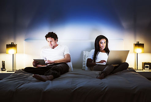 couple using computers in bed